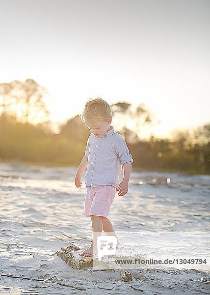 Junge  der bei Sonnenuntergang auf Felsen am Strand gegen den Himmel steht