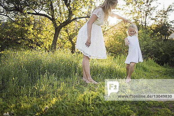 Schwangere Mutter tanzt mit Tochter auf Grasfeld im Park