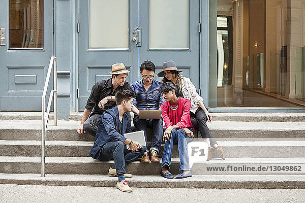 Creative business people using laptop while sitting on steps