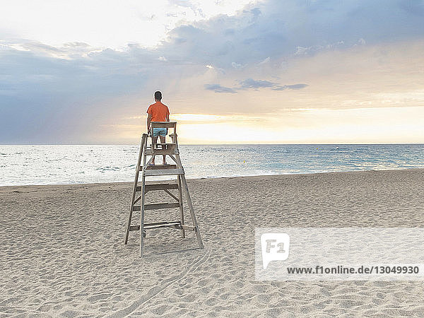 Rear view of man standing on lifeguard hut at beach against cloudy sky during sunset