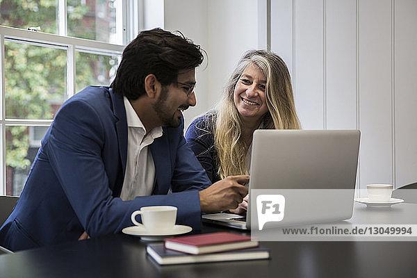 Lächelnde Geschäftsleute diskutieren über Laptop-Computer am Schreibtisch im Büro