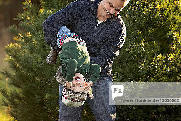 Playful father carrying son upside down against plant at park