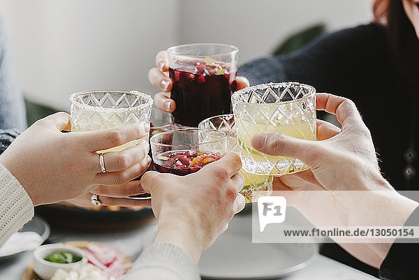 Cropped hands of friends toasting drinks in party at home
