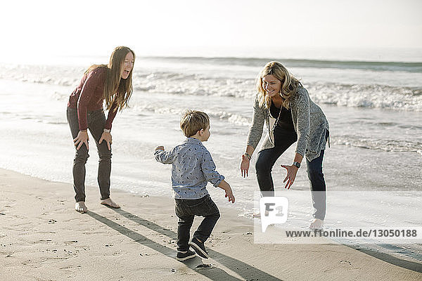 Lesbian mothers playing with son at beach against sea and sky during sunny day