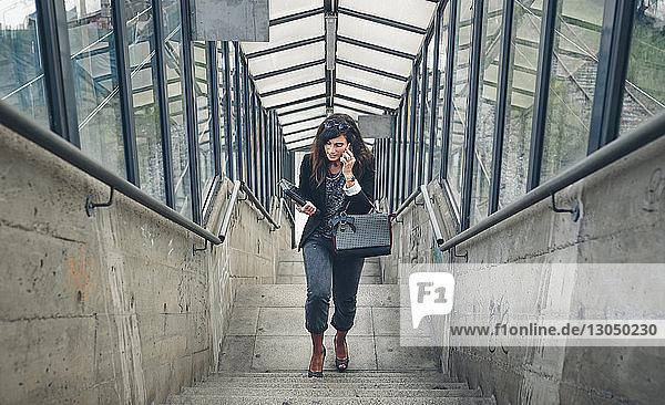 Schrägansicht einer Frau  die beim Treppensteigen mit dem Handy telefoniert