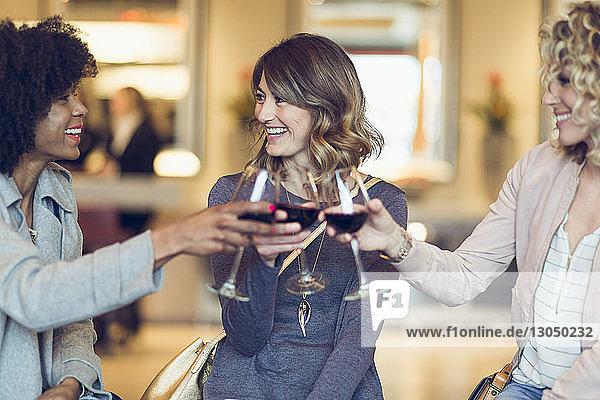 Cheerful businesswomen toasting wineglasses in hotel