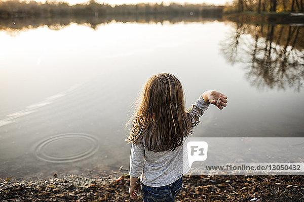 Rear view of girl skimming stones in lake
