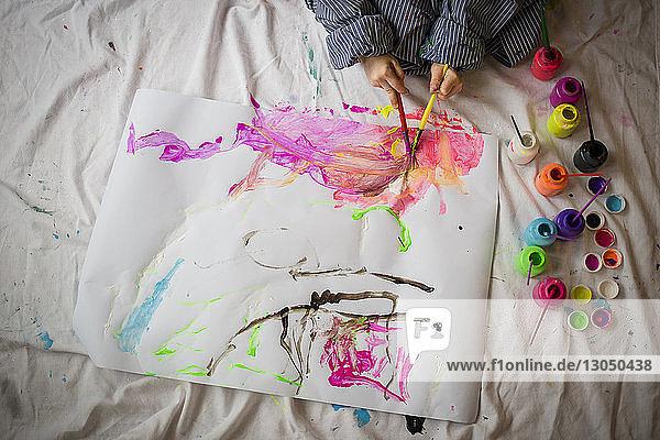 Hochwinkelansicht eines Jungen  der zu Hause sitzend auf Papier malt