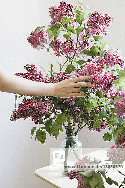 Geschnittene Hand einer Frau,  die Blumen auf dem Tisch berührt
