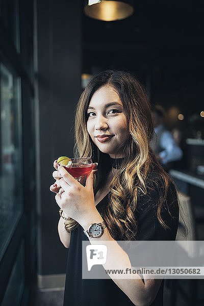 Portrait of confident businesswoman holding drink while standing in hotel