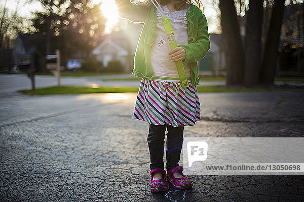 Low section of girl playing with toy while standing on footpath