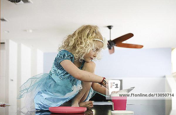 Mädchen entnimmt Essen aus Behälter  während sie zu Hause am Tisch sitzt
