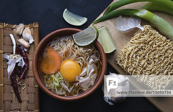 Overhead view of instant noodles soup with ingredients on table