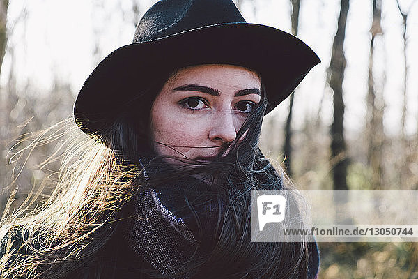 Porträt einer selbstbewussten jungen Frau mit Hut im Park