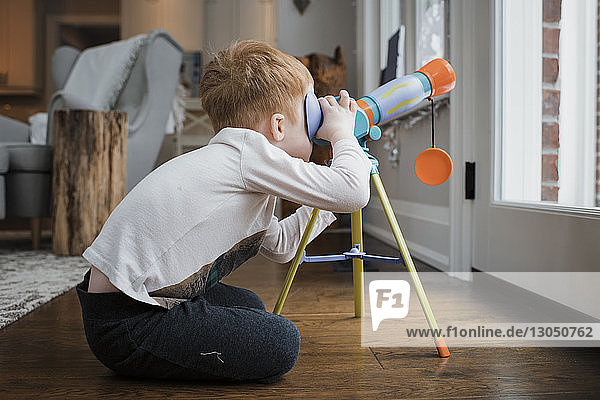 Side view of boy looking through telescope while sitting by door at home