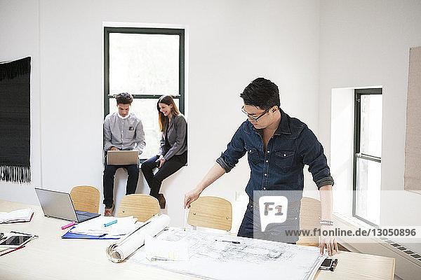 Geschäftsmann analysiert Blaupausen  während Kollegen im Hintergrund einen Laptop benutzen Geschäftsmann analysiert Blaupausen, während Kollegen im Hintergrund einen Laptop benutzen