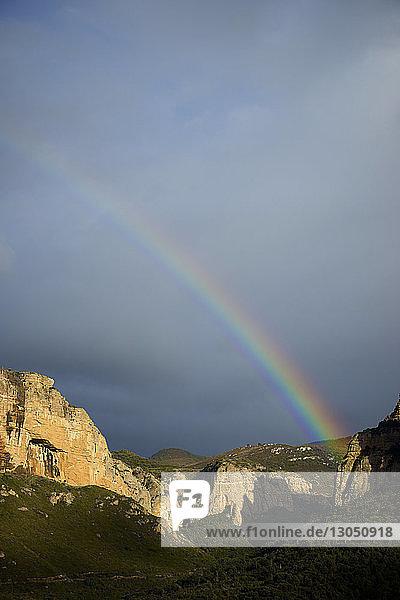 Landschaftliche Ansicht des Regenbogens über den Bergen vor bewölktem Himmel