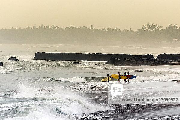 Freunde mit Surfbrett am Strand gegen den Himmel stehend
