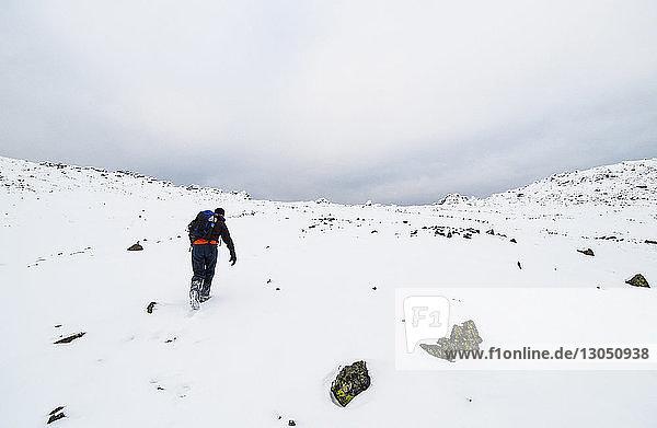 Rückansicht eines Mannes  der auf schneebedeckter Landschaft vor bewölktem Himmel geht