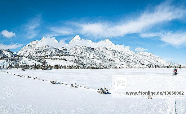 Männer gehen auf Feld gegen schneebedeckten Berg