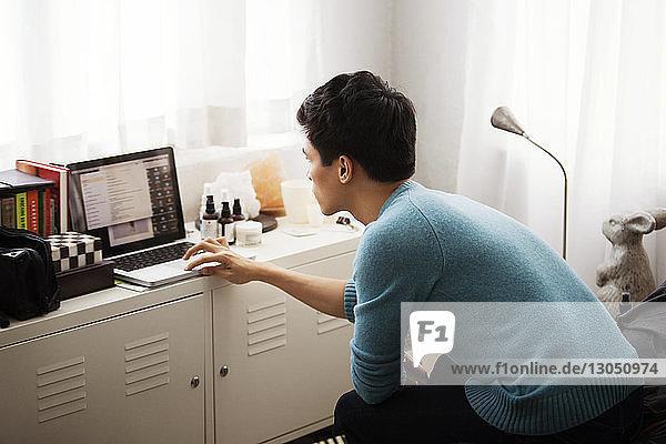 Seitenansicht eines Mannes mit Laptop im Schlafzimmer