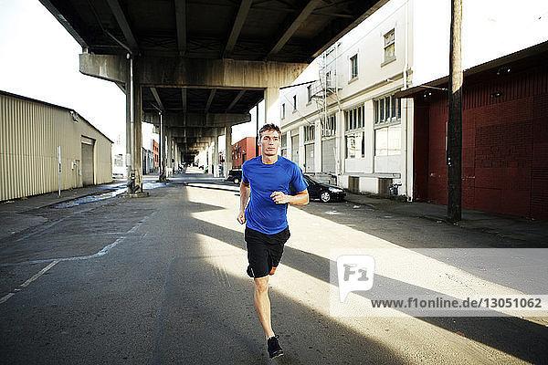 Mann joggt auf Stadtstraße unter Brücke