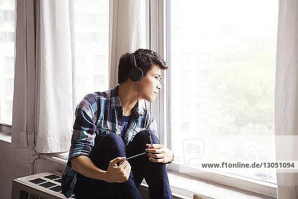 Nachdenklicher Mann hört Musik  während er zu Hause durchs Fenster schaut