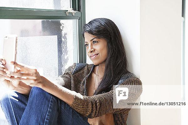 Lächelnde Geschäftsfrau,  die sich durch ein Smartphone selbstständig macht,  während sie auf dem Fensterbrett in einem kreativen Büro sitzt