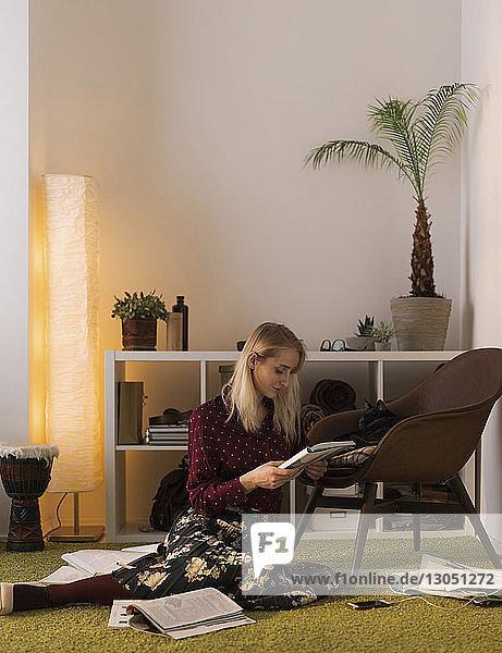 Frau lernt  während sie zu Hause auf dem Teppich sitzt