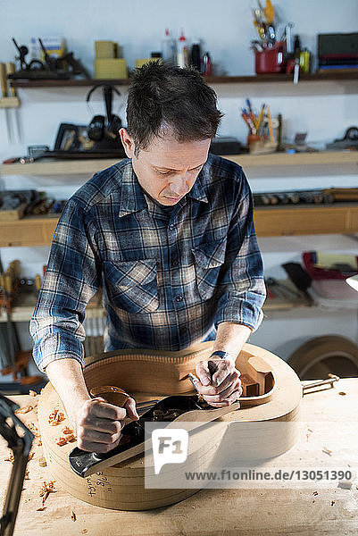 High angle view of man making guitar while working in workshop