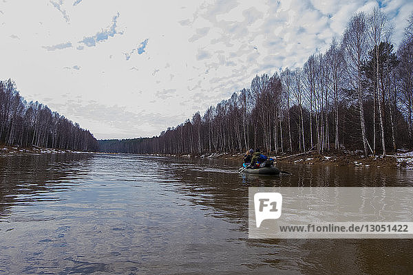 Rear view of friends oaring boat in lake by trees against cloudy sky