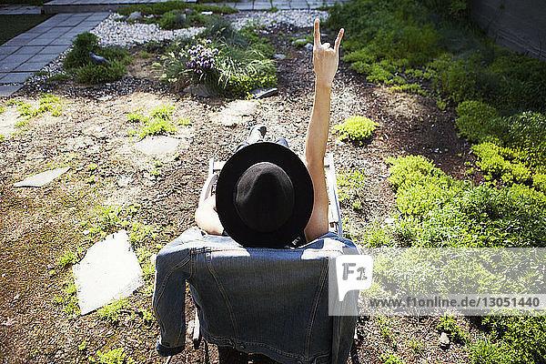 Rückansicht einer Frau  die auf einem Liegestuhl auf einer Terrasse sitzt und dabei ein Hornschild gestikuliert