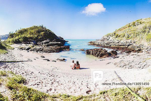 Rückansicht eines Paares  das sich an der Küste am Strand gegen den Himmel entspannt