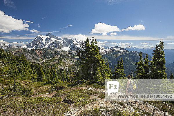 Wanderin in voller Länge  die im Winter im North Cascades National Park gegen Berge und Himmel wandert