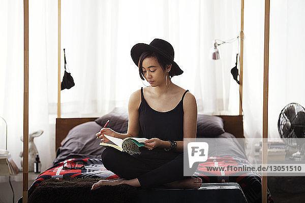 Frau liest zu Hause auf dem Bett sitzend ein Buch