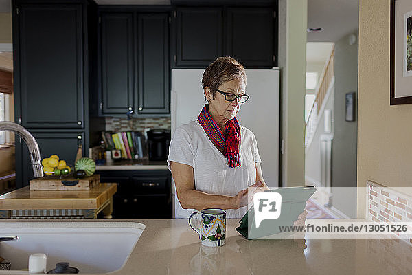 Woman using tablet computer while standing in kitchen