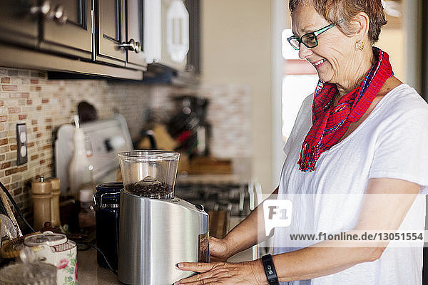 Happy woman grinding coffee beans in electric grinder at home