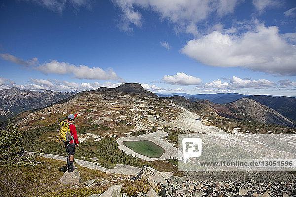 Rückansicht eines Wanderers mit Rucksack in Richtung Berge vor bewölktem Himmel