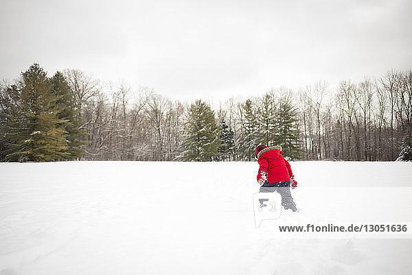 Rückansicht eines Jungen  der auf einem schneebedeckten Feld vor klarem Himmel spielt
