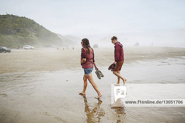 Paar hält Schuhe beim Strandspaziergang im Urlaub