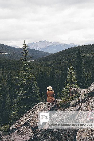 Rückansicht einer Frau  die auf einem Felsen sitzt und die Aussicht betrachtet