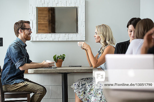 Side view of couple holding coffee cups while sitting at cafe table