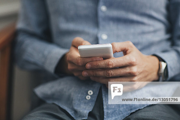Midsection of man using smart phone while sitting on chair