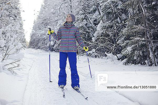 Frau mit Skiausrüstung schaut auf  während sie auf einem schneebedeckten Feld steht