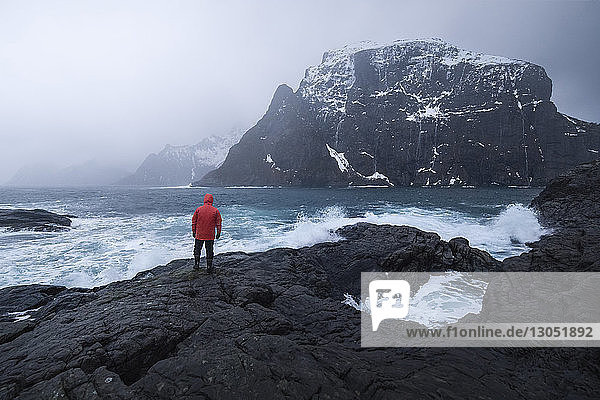 Rear view of man standing at rocky shore during foggy weather