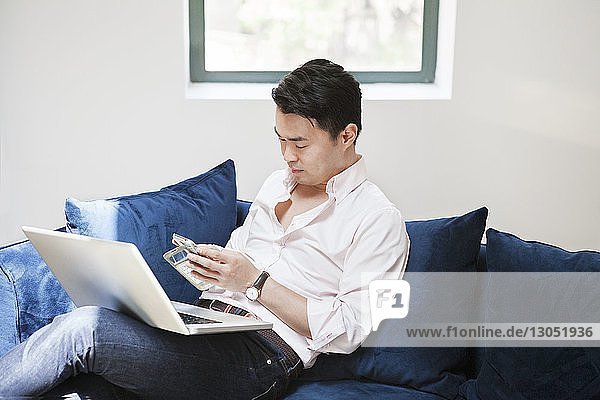 Businessman using smart phone while sitting with laptop on sofa in creative office