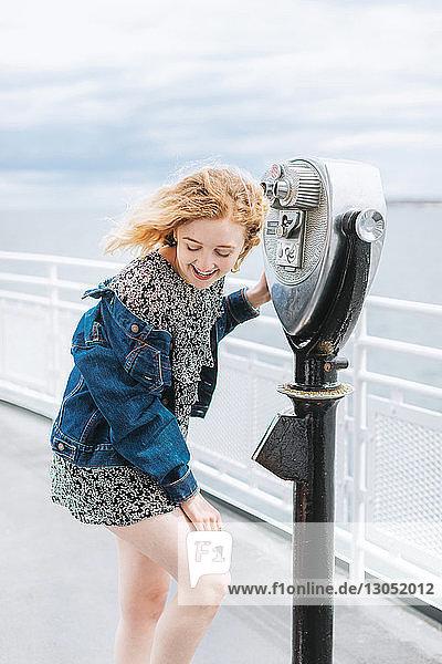 Junge Frau mit einem münzbetriebenen Fernglas am Pier  Menemsha  Martha's Vineyard  Massachusetts  USA
