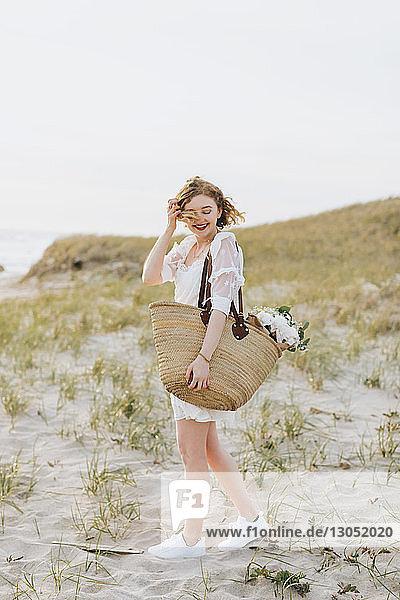 Junge Frau trägt Umhängetasche mit Blumen auf Küstendünen  Menemsha  Martha's Vineyard  Massachusetts  USA