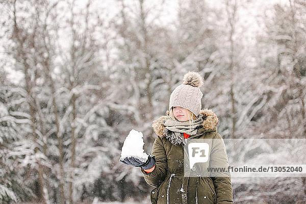 Mädchen mit Schneeball in Winterlandschaft