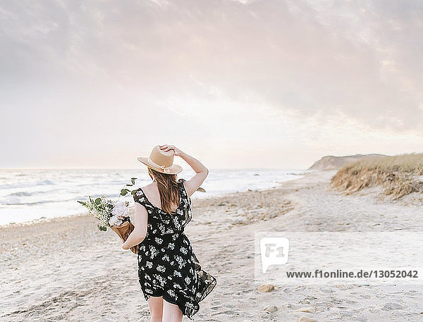 Young woman strolling with bunch of flowers on windy beach  rear view  Menemsha  Martha's Vineyard  Massachusetts  USA